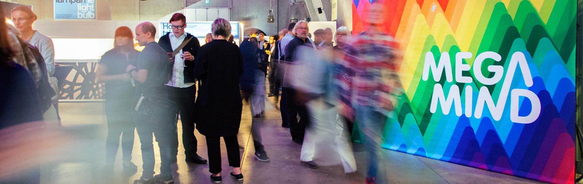 Många människor minglar i en utställning.