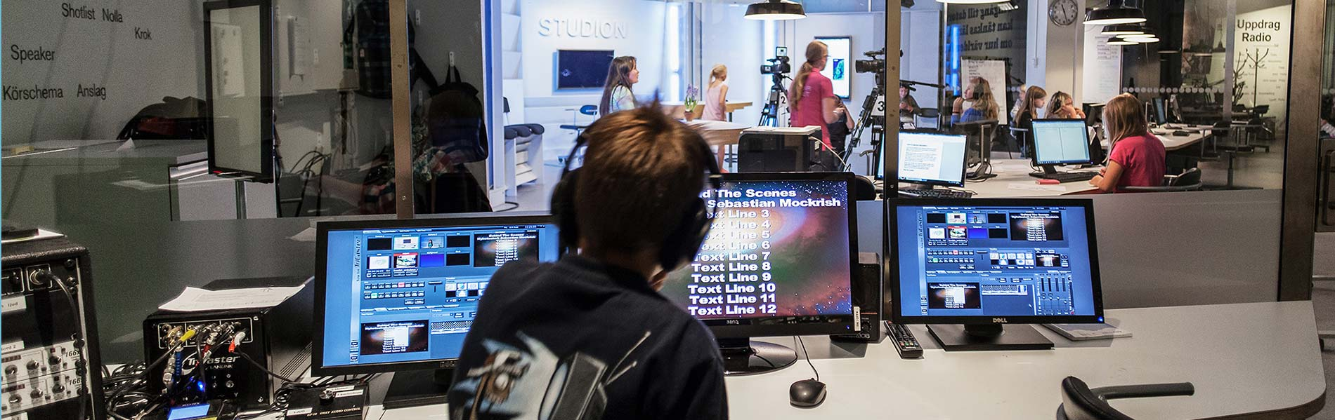 Pojke i kontrollrum med TV-studion i bakgrunden.