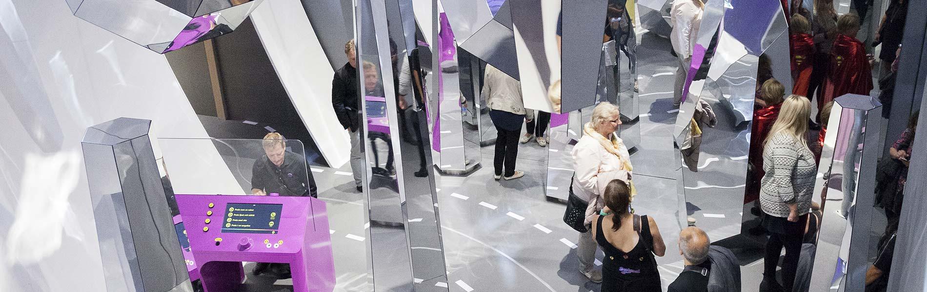 Personer går runt bland speglar i olika formationer.