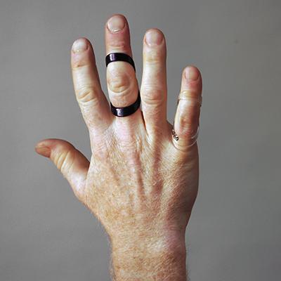 En hand med en svart stödfunktion för långfingret