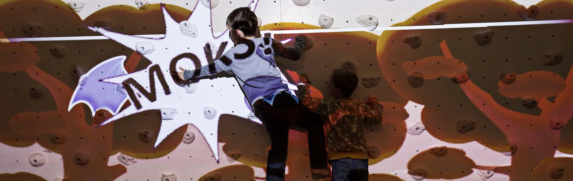 Barn spelar dataspel på en interaktiv klättervägg