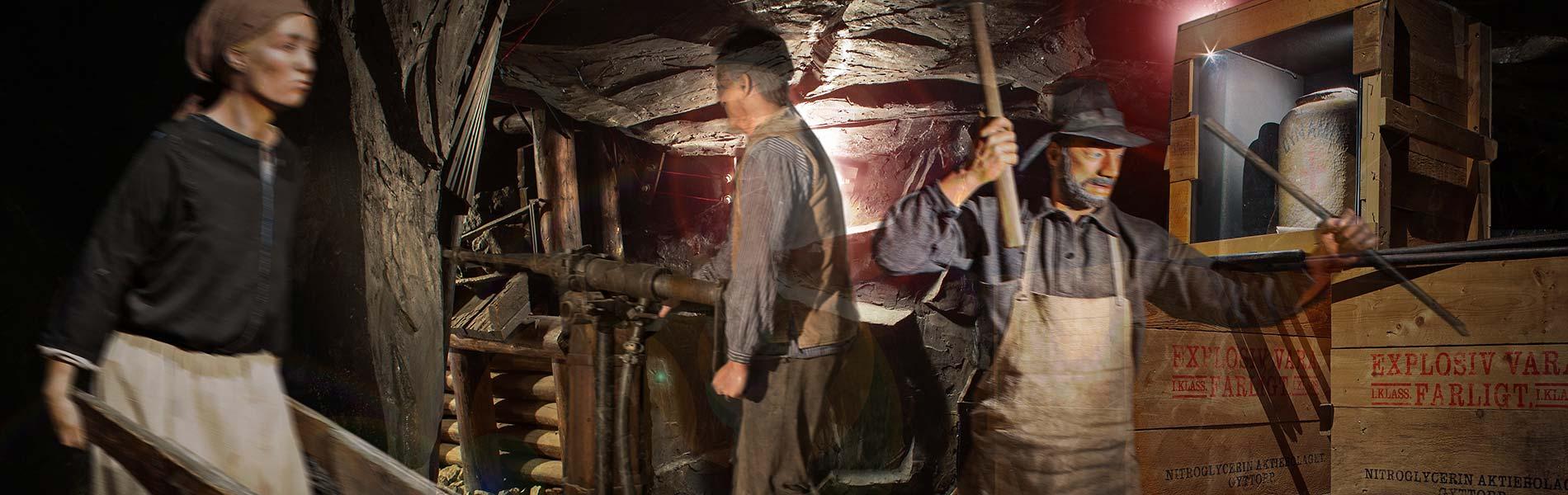 Dockor med gamla verktyg i gruvmiljö från förra sekelskiftet