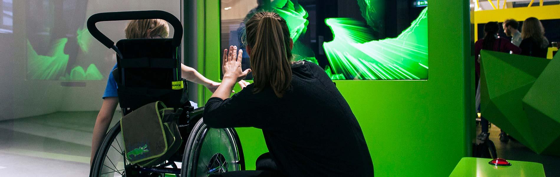 Pojke i rullstol formar skulptur med händerna i luften på skärm
