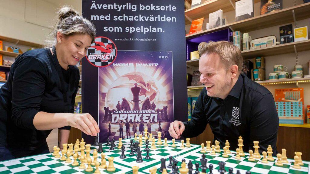 kvinna och man ser glada ut när de spelar schack.