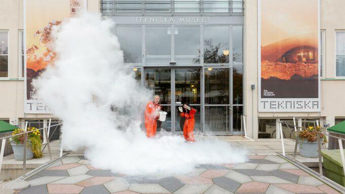 man och kvinna experimenterar med kväve framför tekniska museets entredörr.