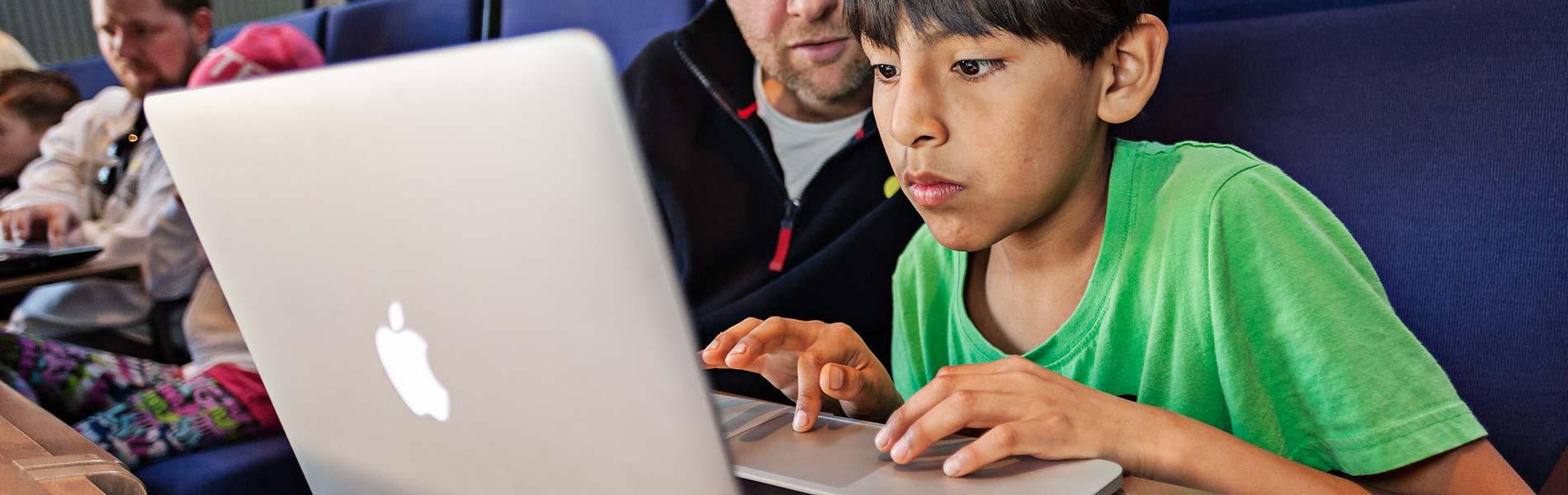 Man och pojke vid bärbar dator