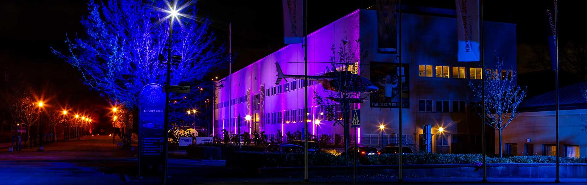 Tekniska museets fasad kvällstid med blå-lila belysning