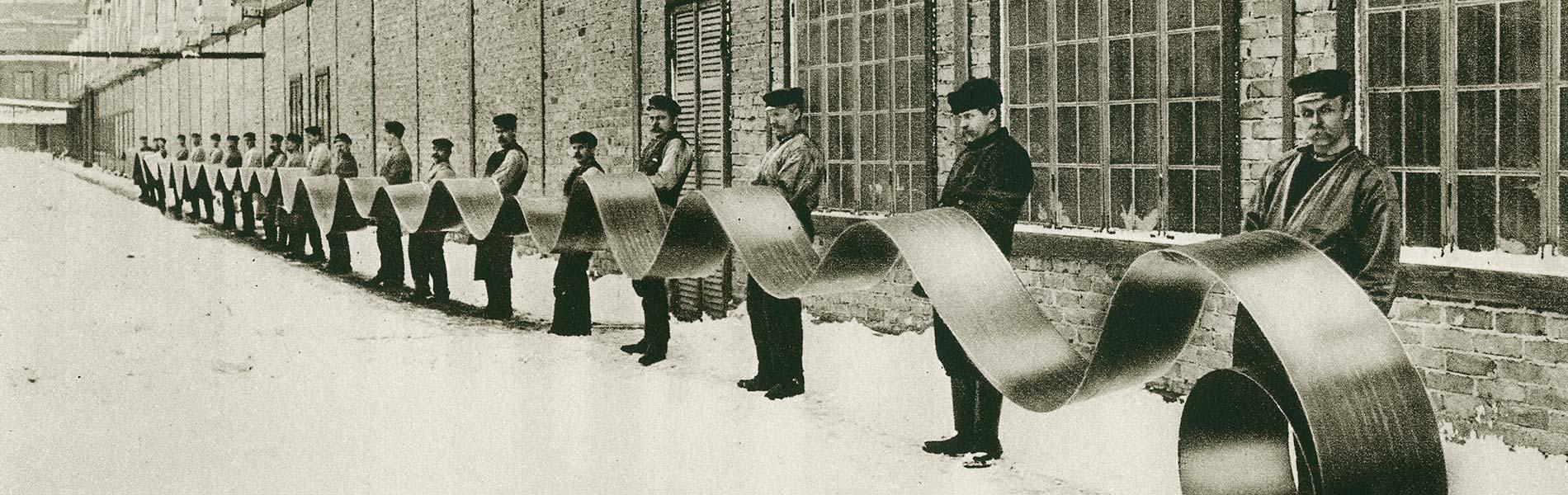 Arbetare håller i ett stålband