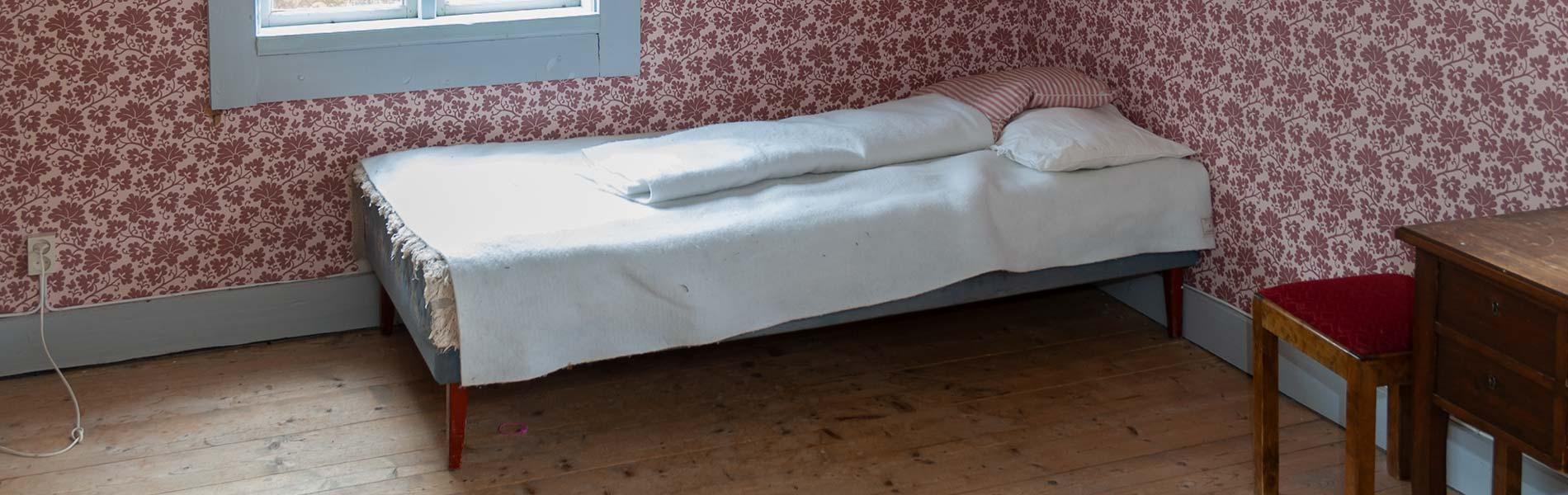En säng med vita lakan står i hörnet av ett rum