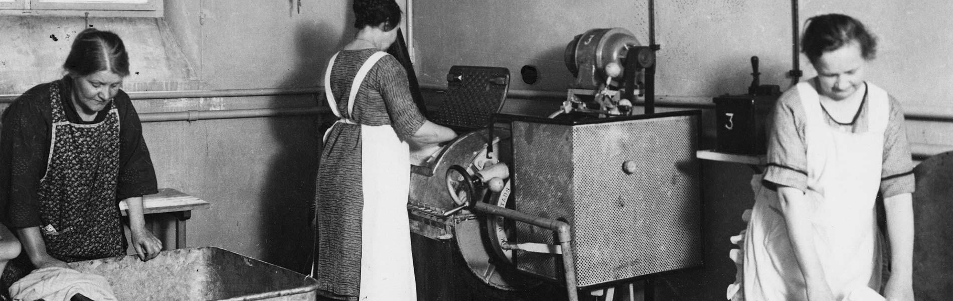 En kvinna står framför en stor tvättmaskin. Bakom henne ligger en tvättkorg med linne