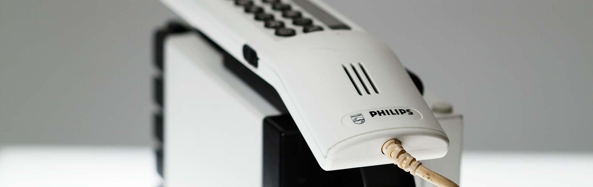 En vit och svart mobiltelefon. Den är stor och tung