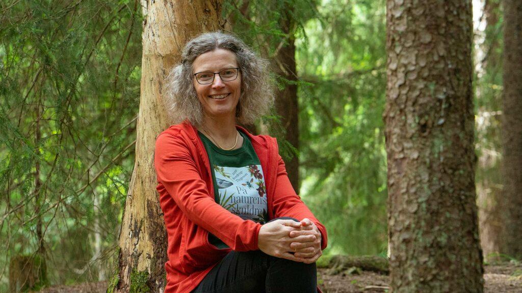 äldre kvinna ute i skogen och sitter på en stubbe
