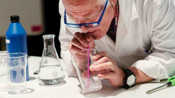Äldre man som genomför ett experiment med ett glas och sugrör