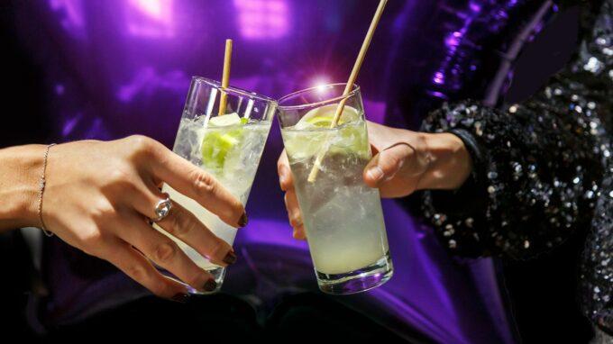 två händer som skålar med varsin drink